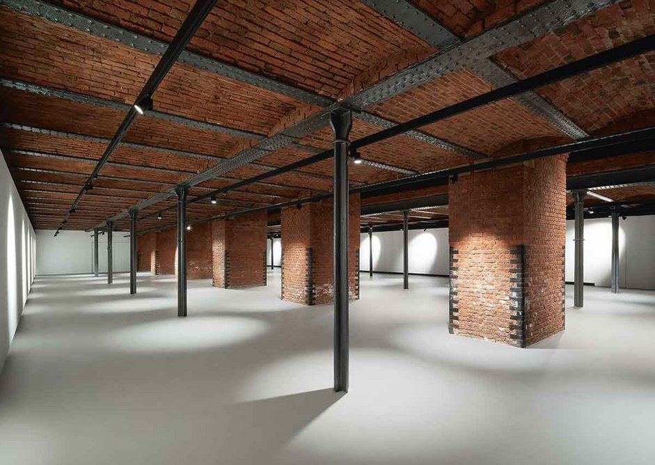A pigeon grey concrete floor finish benignly offsets the colour and complexity of the flat arched, cast iron structure supporting the museum's New Warehouse space above.