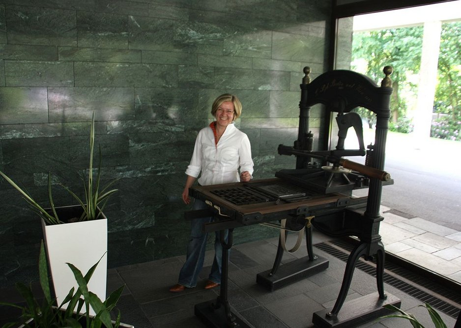 Maria Heyer-Dombrink alongside an early 19th century press in the firm's 1950s lobby.