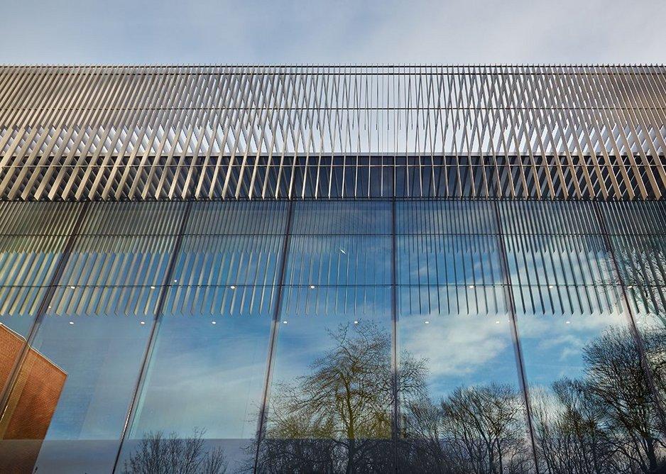 The lighweight brises soleil reflected alongside the park trees.
