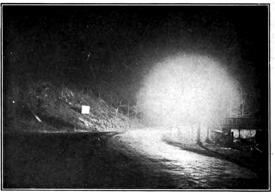 """Glare is as much a matter of placement as absolute brightness.  Here, """"serious glare"""" is created by a lamp placed at the curve of a country road, obscuring cars approaching from beyond the curve.   Preston Millar, """"The Effective Illumination of Streets,"""" Transactions of the American Institute of Electrical Engineers 35 (June, 1915)."""