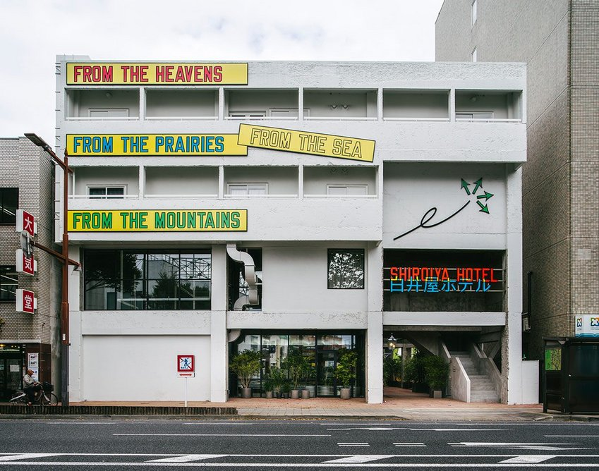 The façade is emblazoned with a bold text artwork by conceptual artist Lawrence Weiner.