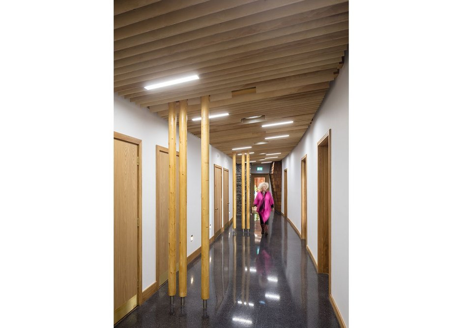 A single route through the building with services on one side and larger volumes facing into the landscape beyond.