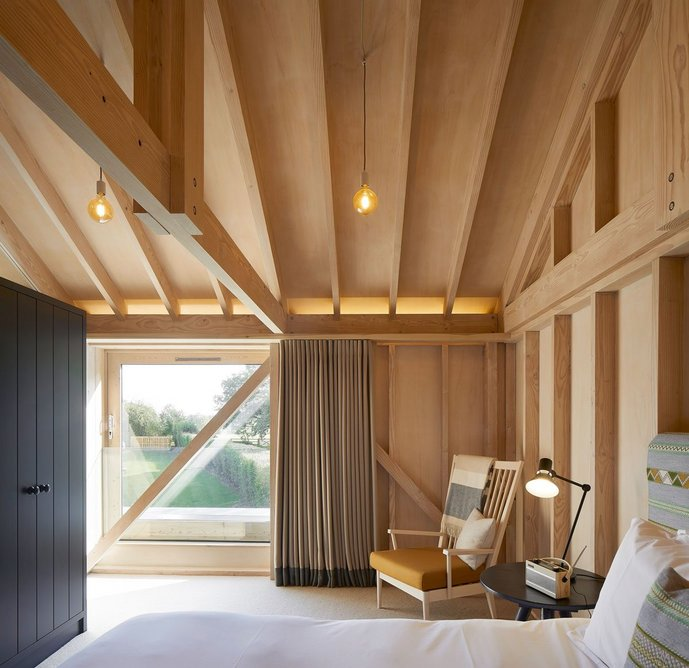 The expressed timber structure suggests agricultural buildings, but is  luxuriously reinterpreted.