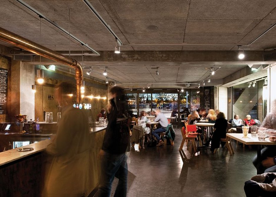 Inside the new Understudy Bar: Haworth Tompkins has kept the rough finishes of these former service spaces.