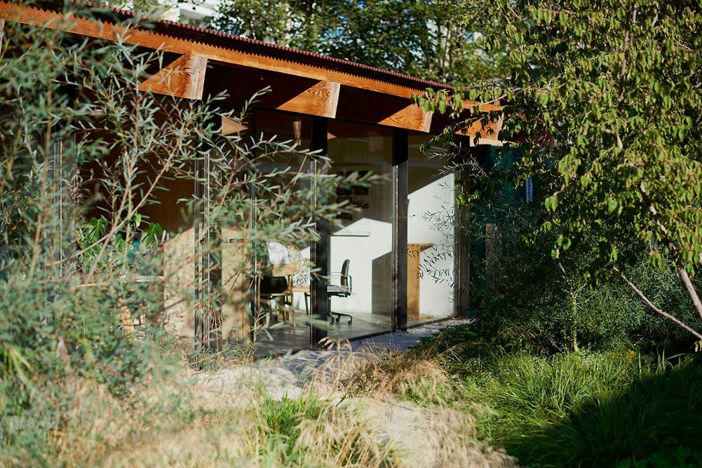 The timber beams of Feilden Fowles' studio cantilever outdoors to support a covered walkway.