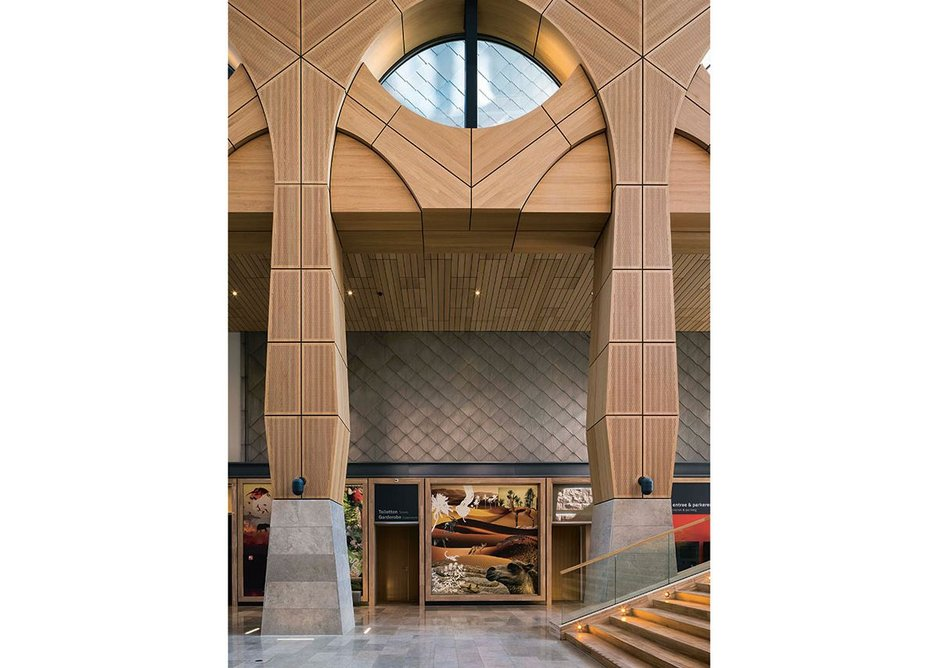 Set against the metal cladding of the archive tower, the hybrid structure of the atrium is clad from top to bottom in perforated European oak.