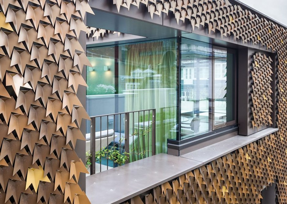 The metal-clad façade, inspired by nearby Virginia creepers, is inset with Schueco window systems.