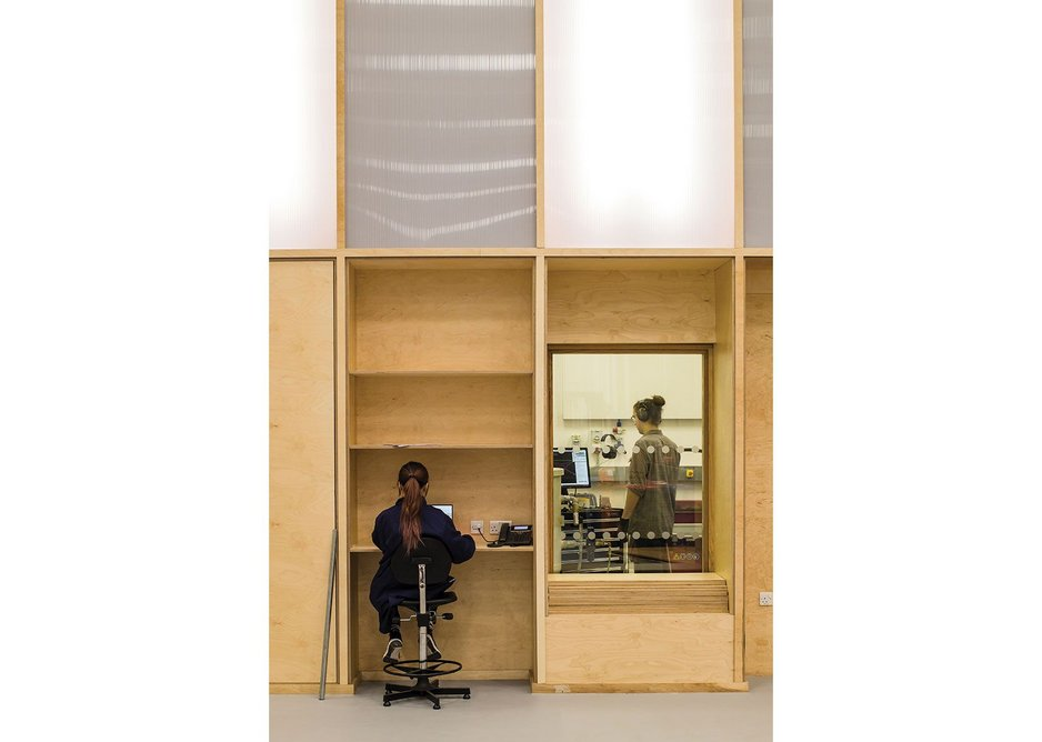 A plywood utility wall runs the length of the runway, incorporating touchdown areas and views through to the laboratories beyond.