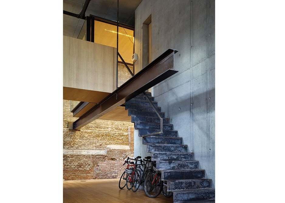 An apparently cantilevering single beam supports the meeting room box, accessed by a folded steel stair.