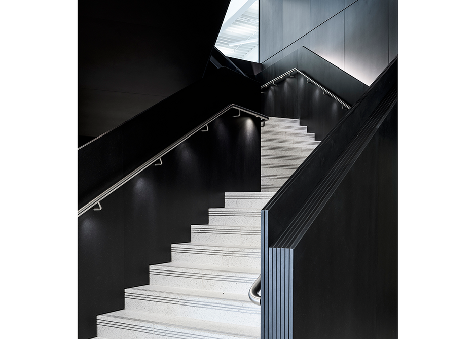 Handyside Street by Coffey Architects. Main staircase, where black cladding creates a dark prelude before emerging into the contrastingly bright and expansive office floors. Photo © Tim Soar.