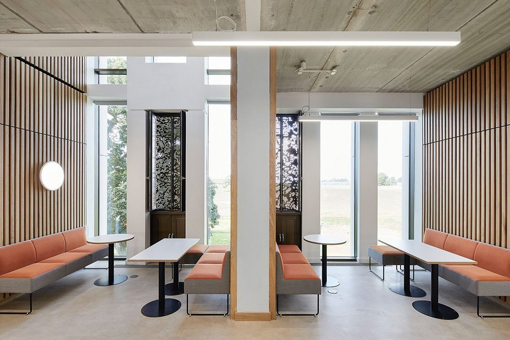 Timber-lined meeting areas align the top-lit principal circulation route.