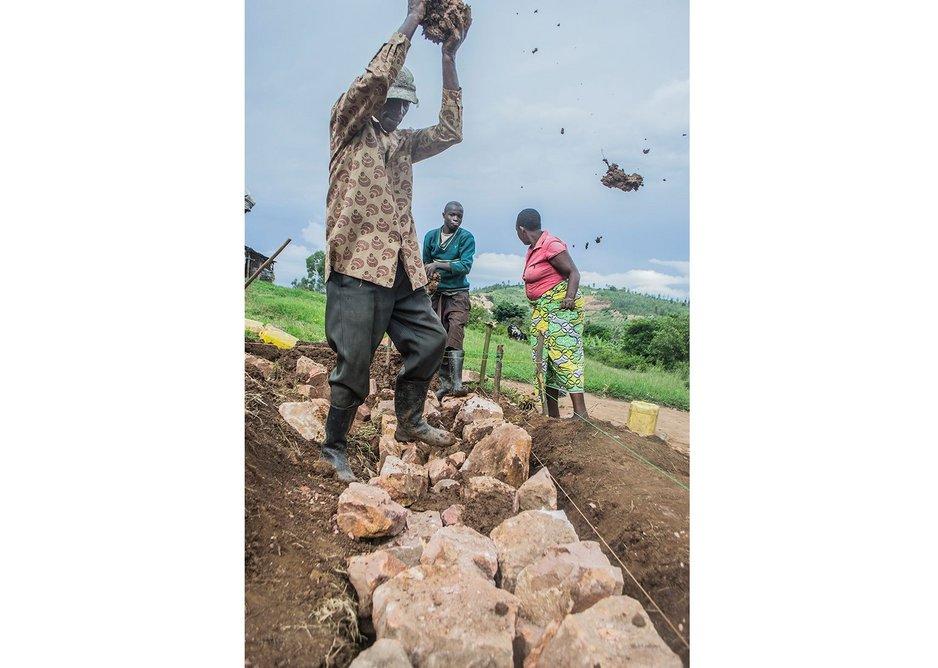 Damacent slams wet mud mortar into the foundation joints, Ntarama, Rwanda, November 2014.