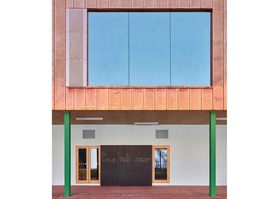 A new copper box of classrooms partially supported by green stilts replaces the roof of one wing to the courtyard.