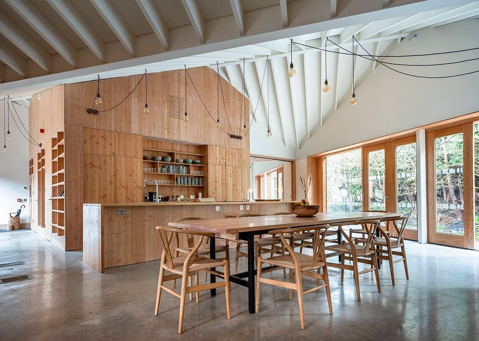 Exposed rafters rest on white painted steels about the CLT walls giving a lofty space above the Maggies' kitchen table.