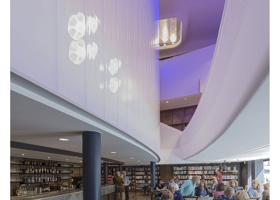 Under the mezzanine the curves continue above the bar and into the cast glass encasing the cinema. Chester Storyhouse, Bennetts Associates.