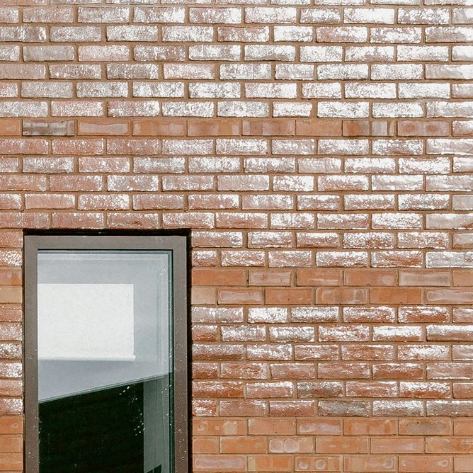Bands of glazed bricks get broader as they move up the front elevations.