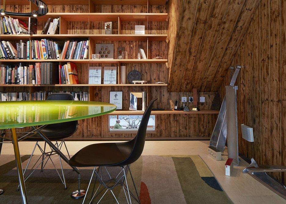 The mezzanine office is illuminated by its green table. A timber lining re-uses the wood from the stationers that was previously on the site.