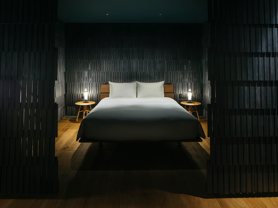 A special room by Michele De Lucchi has an intimate interior painstakingly layered in 2,725 black curved-edge wood shingles, traditionally used in roofing.