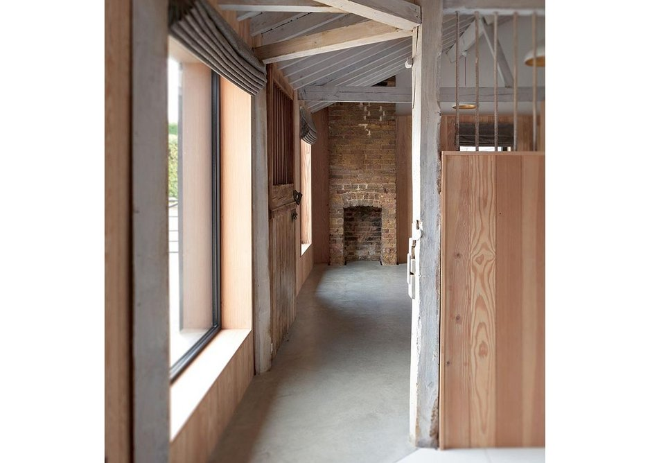 The open plan ensuite guest bedroom nestles in the original stable stalls.