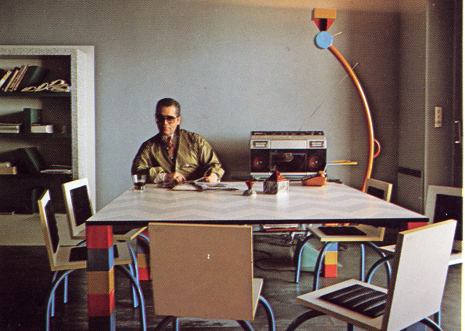 Karl Lagerfeld in his Monte Carlo apartment, with designs from Memphis' first collection in 1981. These include Pierre table by Sowden, Riviera chair by De Lucchi, Treetops lamp and Suvretta bookcase by Sottsass. Ceramics by Matteo Thun. Memphis 1981. From the book Memphis, Research, Experience, Results, Failures and Successes of the New Design by Barbara Radice, ed Electa. Photo: Jacques Schumacher. Copyright Mode & Wohnen.