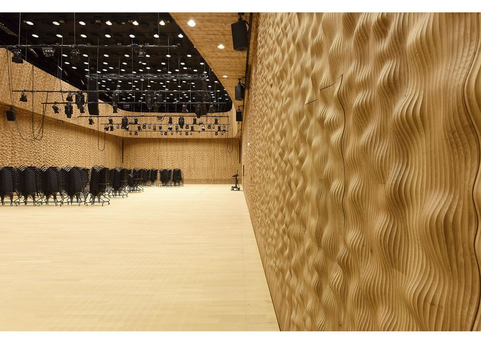Acoustic walls formed of thousands of oak dimples enliven the conventional box form of the Recital Hall.
