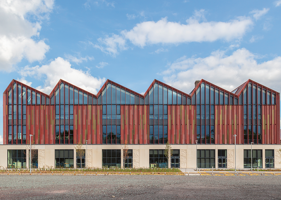 With an MMC aesthetic, the west elevation has repeating bays of precast concrete, vertical louvres and metal panels. The architecture studio runs below the length of the roof.