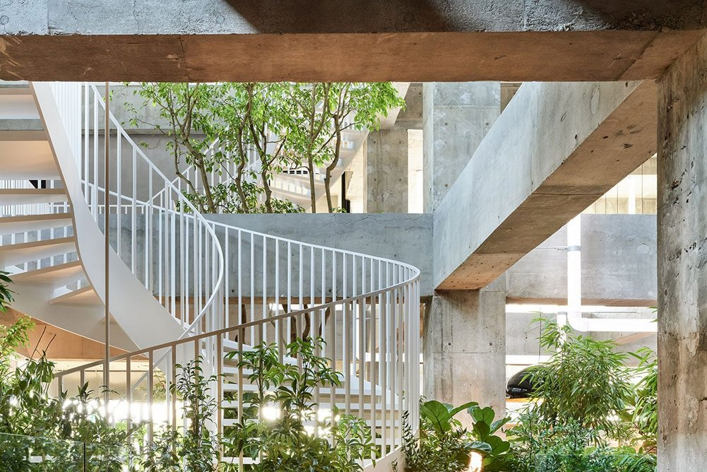 The atrium of the Shiroiya Hotel, housed in a former 1970s hotel, excavated into a minimalist shell by Fujimoto, complete with a spiral staircase, plants and ceilings stretching 15 metres high.