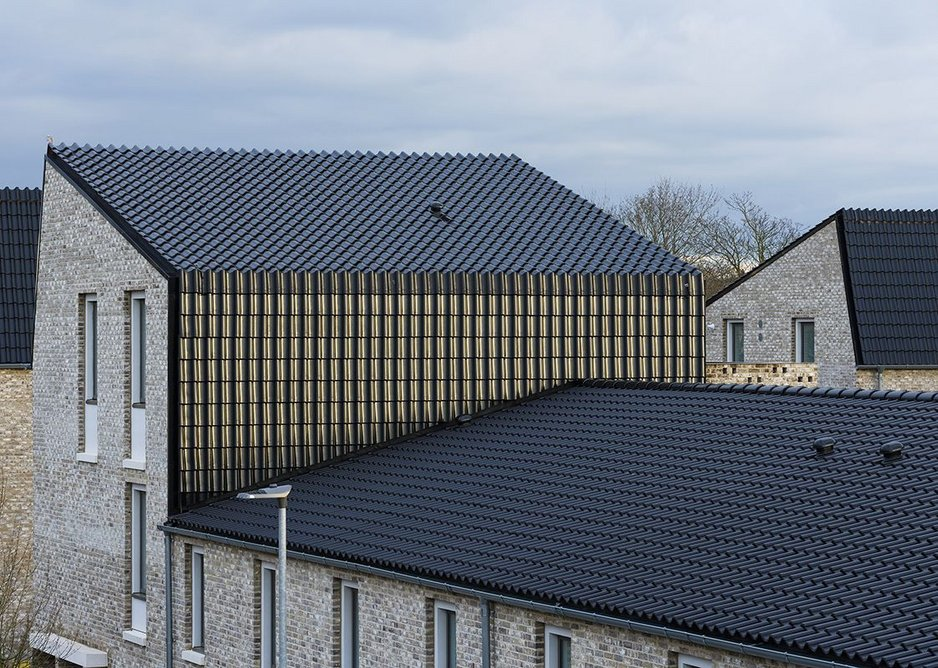 Black pantiles clad the rooves and elevations of the end of terrace blocks of flats.