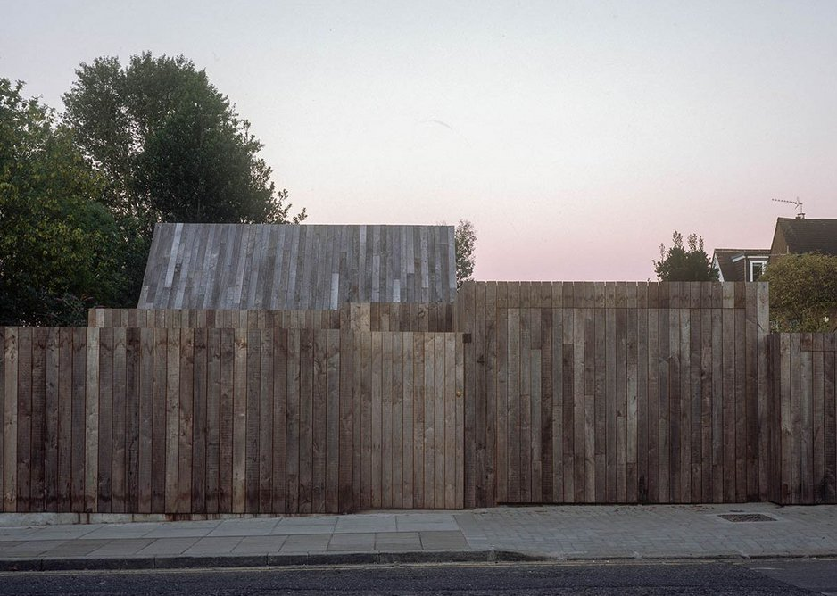 From the street the house appears as layers of timber fencing.