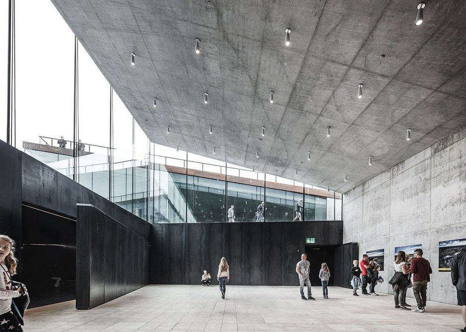 Cantilevered roof slabs allow for full height glazing to the halls, counterpointing the darkness of the bunker itself.