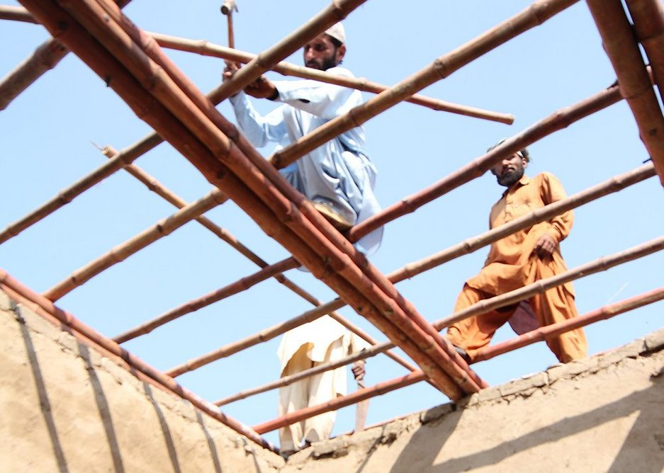 Villagers put a roof on mud hut built to Yasmeen Lari's design.