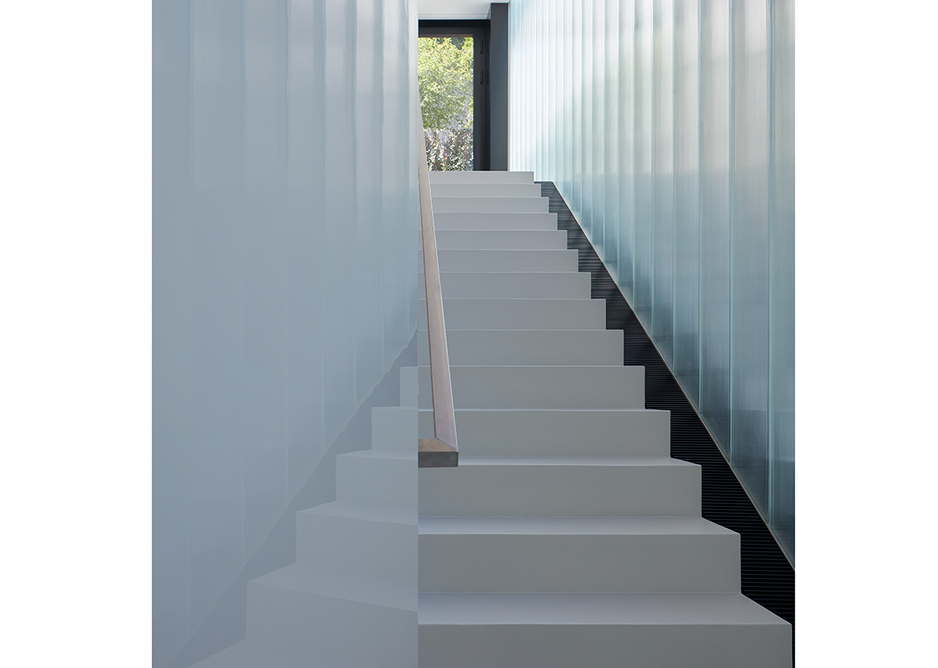 Translucent glass panels line the narrow stairwell.