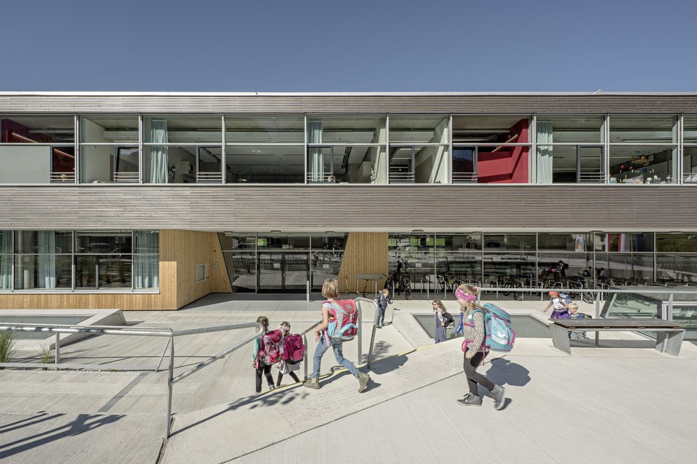 A two-storey building with a slightly lower forecourt along the main road welcomes the pupils.