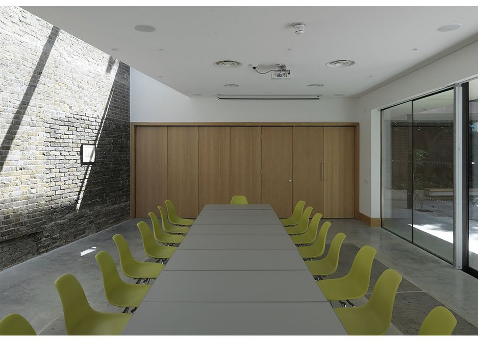 Inside the education room. Behind the wooden doors lies a kitchen, storage and space for organisation.