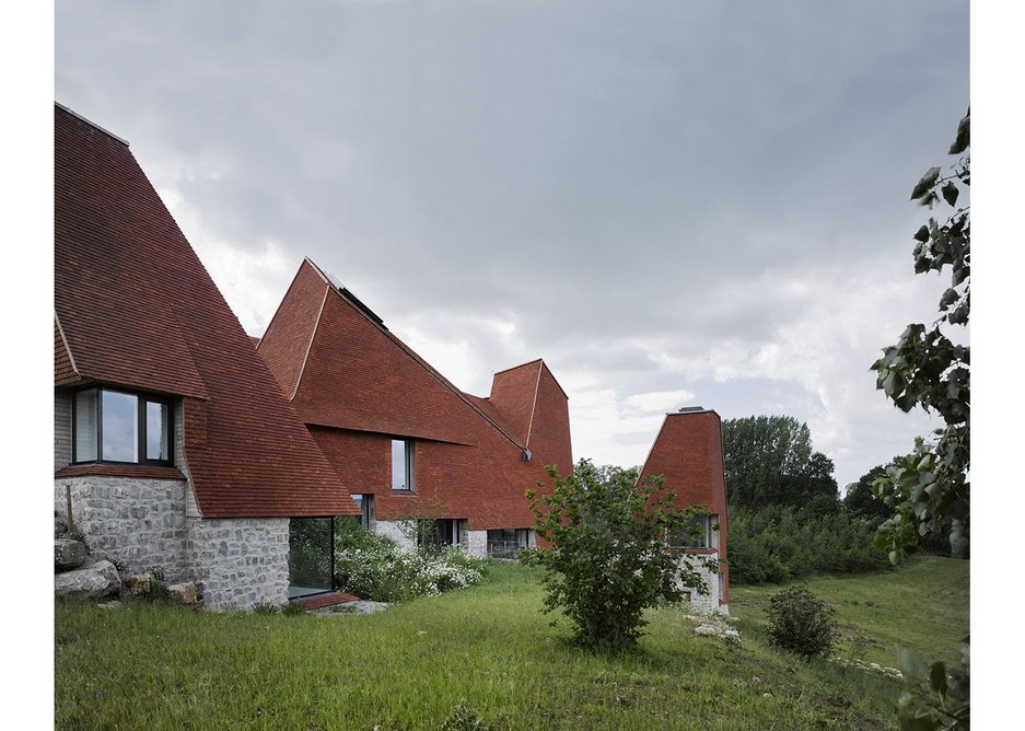 The house occupies a sloping site with views towards Pilgrim's Way.