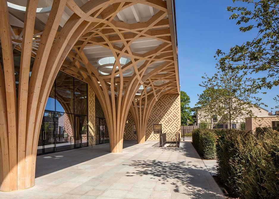A colonnade of structural timber columns supports a portico which is the first experience of the building from the street.