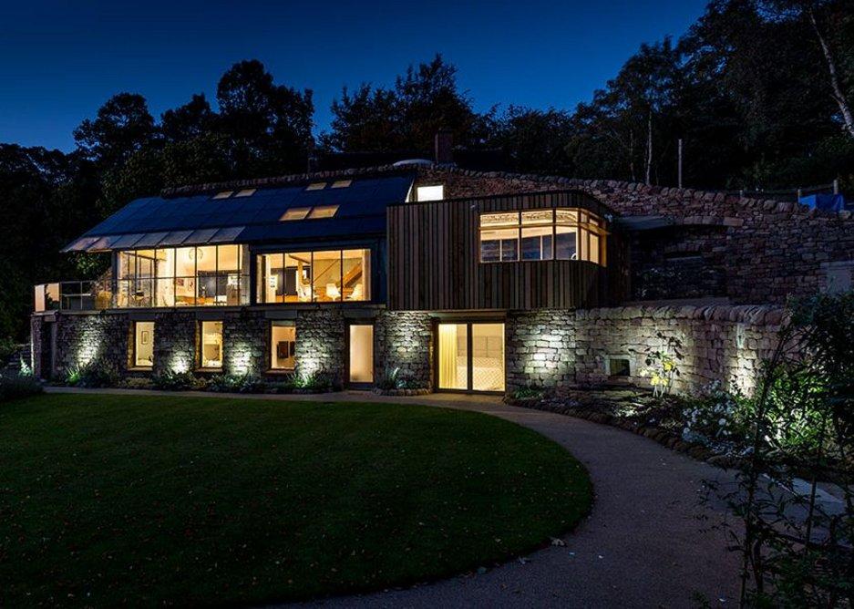 Dusk shot reveals the arrangement of a substantial but self-effacing house.