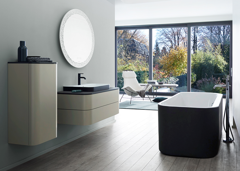 The circle and open oval geometric elements that typify the design are supported by the two-tone colouring of the above-the-counter basins in Anthracite Matt/White and the bathtub with external panelling in Graphite Super Matt.