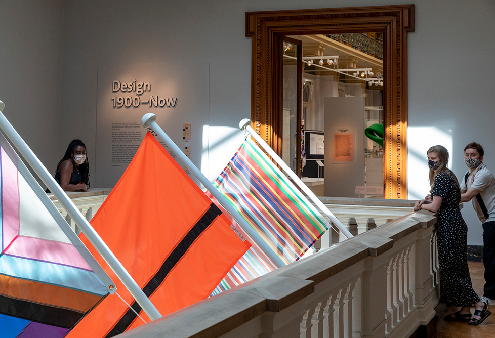 Installation shot of the new Design 1900 – Now gallery at the V&A. Flags include the black and red Refugee Nation flag created to mark the participation of the first ever refugee team in the 2016 Olympics.