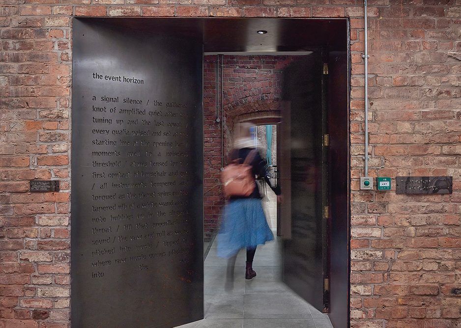 A deep steel-lined portal with Simon Armitage poem cuts through the thick brickwork at the base of the campanile to link new and old buildings.