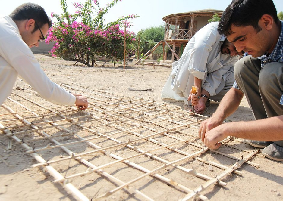 Students make a bamboo lattice for the corners and the walls of the Yasmeen Lari-designed house, to prevent damage during earthquakes.