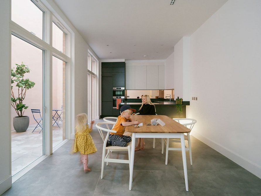 Basement kitchen and dining area of corner house, showing longer courtyard.