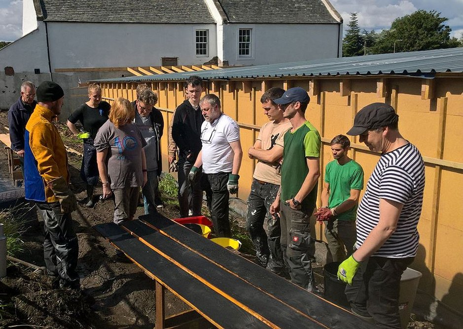 Volunteers being shown how to char the timber cladding on site.