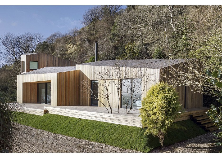 The timber pod forms sit on an anti-seismic raft concealed in the grass plinth.