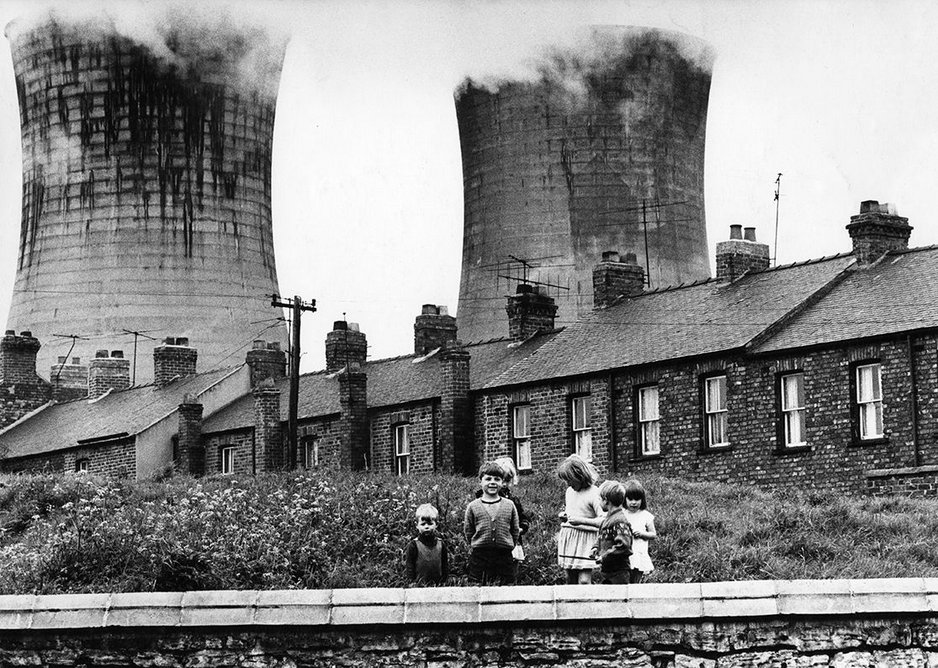 Children posing against the backdrop of workers' housing and industrial cooling towers, Teeside, 1969.