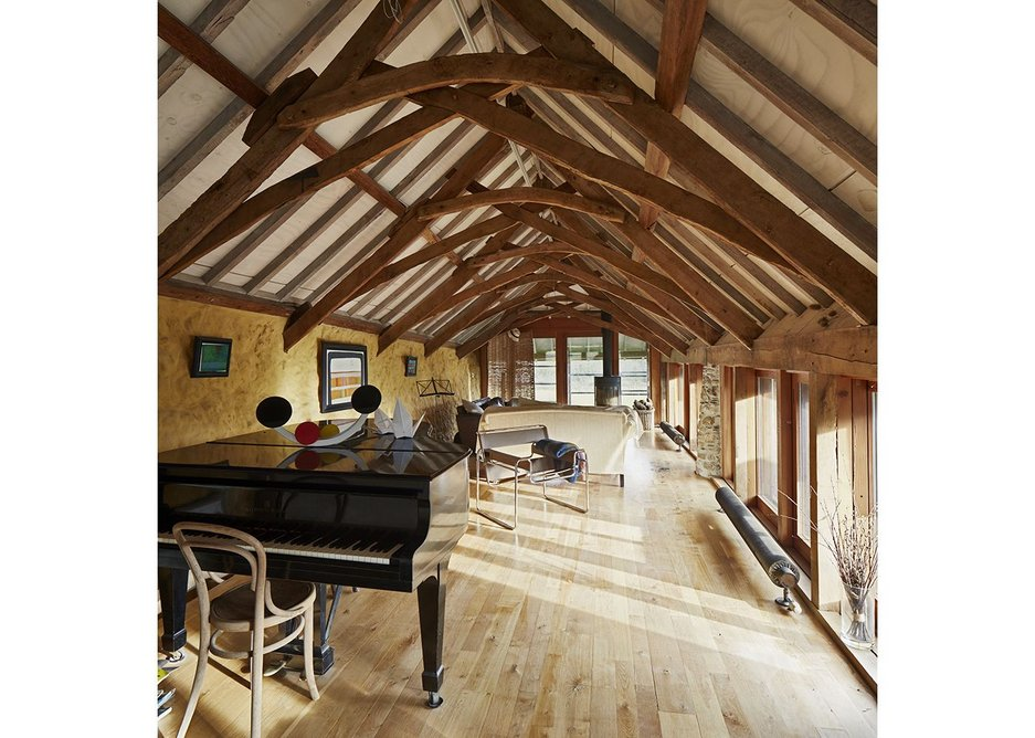 The elevated living room takes advantage of the beautiful roof trusses, new and old.