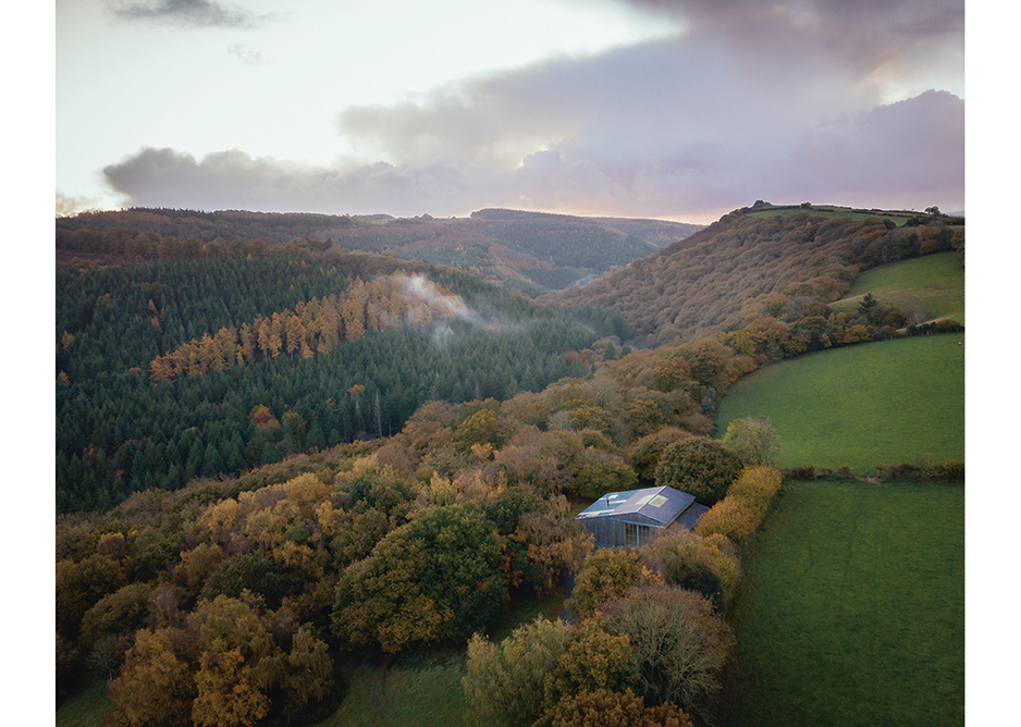 The track leading to the Art Barn enters a 100-acre broadleaf wood cloaking the north bank of the River Teign and arrives at the building's gabled east facade.