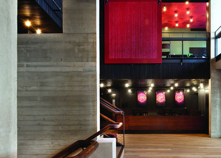 Overlooking the foyer is an events room which can be closed off: the sliding screen is made of lengths of timber used in the concrete shuttering.