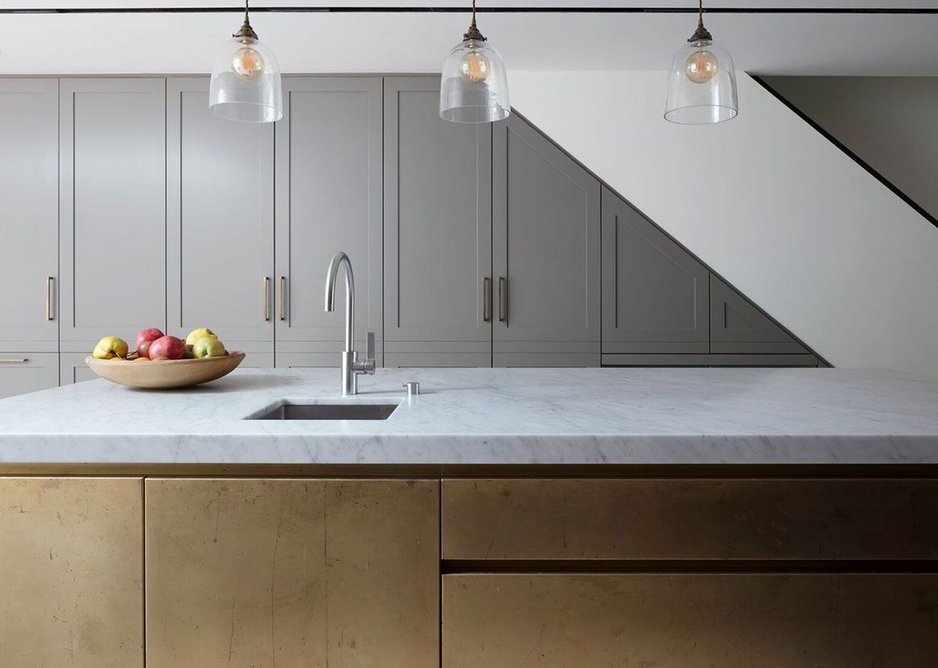 Roundhouse Classic lay-on Urbo painted bespoke kitchen storage with island in brass metal wrap, matt-sanded finish and marble worktop.