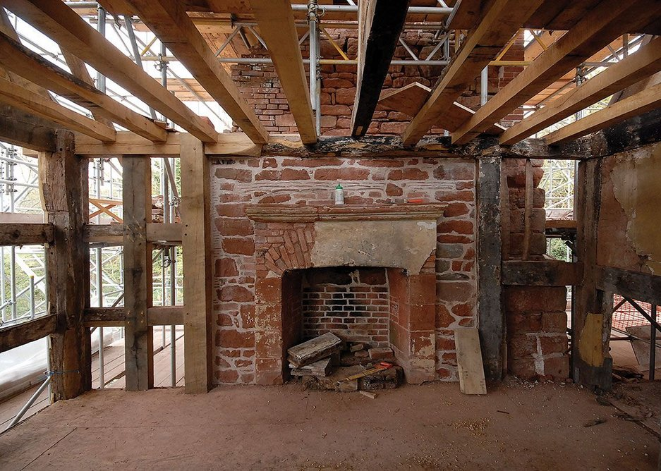 Timber beams, old and new, starting to be put back into place.